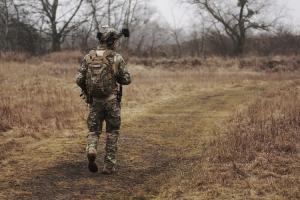Person in military clothing walking down a dirt path